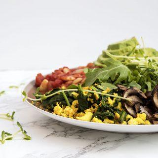 vegan brunch with tofu scramble baked beans potato hash mushrooms and avocado toast